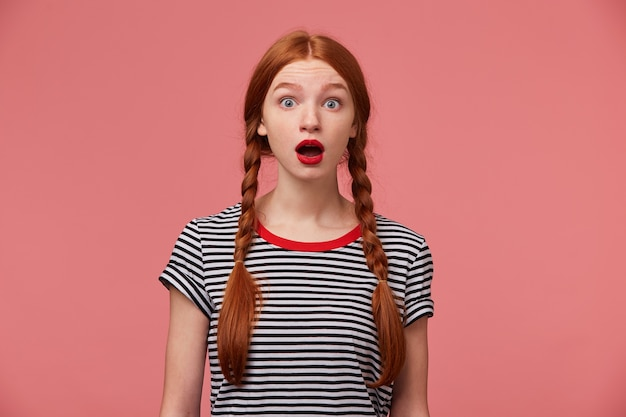 Шокированная женщина с двумя рыжими косами, красная помада, открыла рот в отчаянии и шоке, не зная, что значит встревоженное положение перед огромной проблемой, расстроенная и озадаченная над розовой стеной