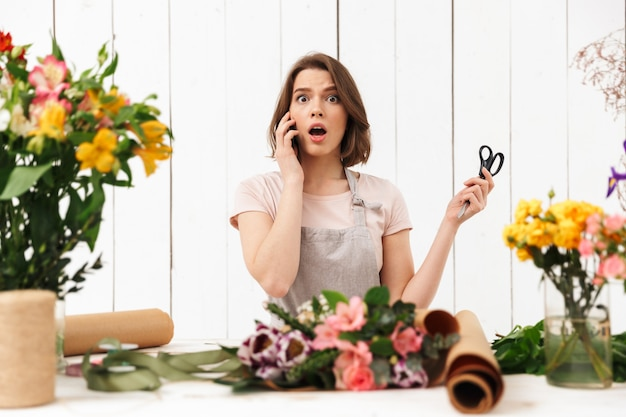 Shocked florist woman standing over a lot of flowers