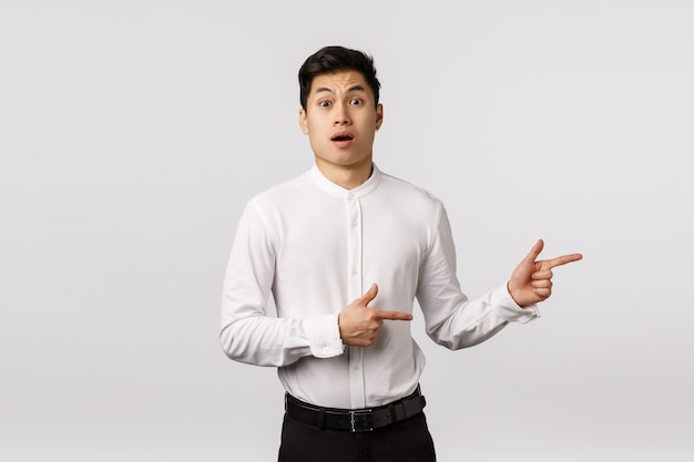 Shocked, freak out concerned cute asian boyfriend hear girlfriend pregnant, gasing shook and astonished, standing speechless open mouth amazement, pointing right indecisive,