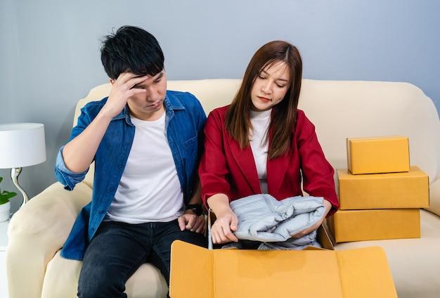 ショックを受けた欲求不満のカップルの顧客が段ボール箱を開けると、間違ったまたは破損したショッピング注文の小包を受け取ります