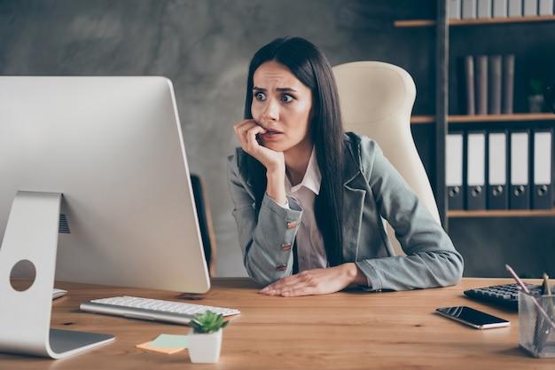충격을 받은 좌절한 소녀 에이전트 작업 원격 보기 화면 컴퓨터 pc 읽기 회사 파산 직원 해고 두려움 물린 손가락 손톱 직장 워크스테이션에서 책상 착용 블레이저 재킷 앉다
