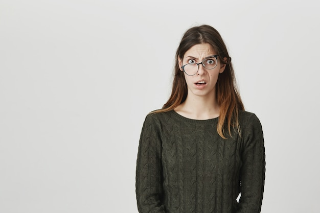 Shocked and frustrated woman with crooked glasses staring camera ambushed