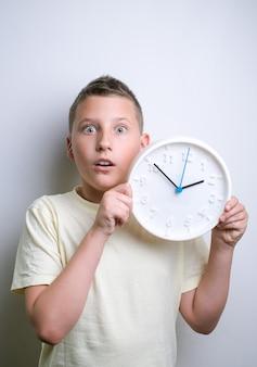 흰색 시계 알람 복사 공간을 들고 충격된 재미 소년 흰색 배경 위에 절연 아이