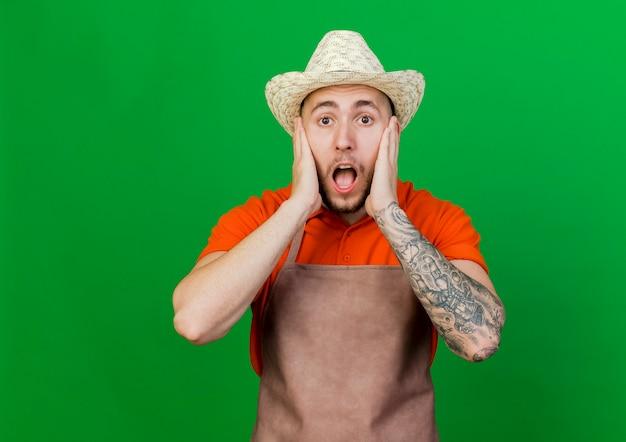 원예 모자를 쓰고 충격을받은 정원사 남자가 얼굴에 손을 댄다.