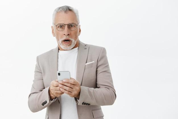 Uomo anziano senza fiato scioccato alla ricerca, utilizzando lo smartphone