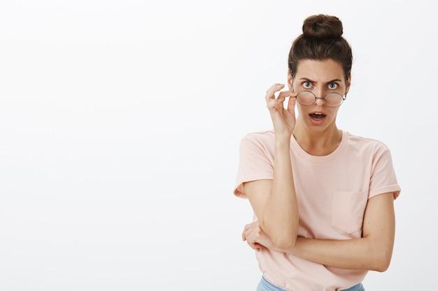 Giovane donna alla moda scioccata senza fiato che posa contro il muro bianco
