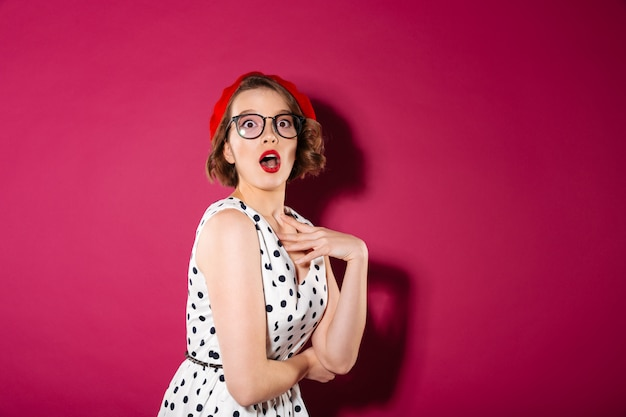 Shocked ginger woman in dress and eyeglasses looking at the camera over pink