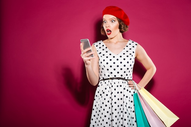Shocked ginger woman in dress with packages using smartphone over pink