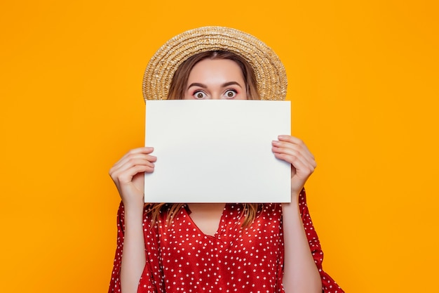 Shocked girl holds an a4 empty poster and covers her face isolated over orange background
