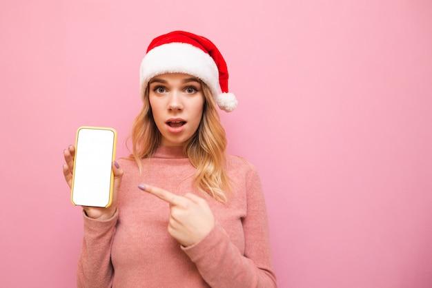 Шокированная девушка в новогодней шапке стоит на розовом, держит в руке смартфон