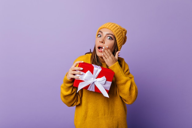 캐주얼 스웨터와 모자 선물 포즈에 충격 된 소녀. 경악을 표현하는 새해 선물을 가진 debonair 아가씨의 실내 초상화.