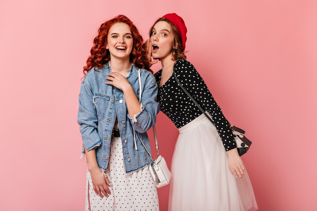 Шокированная девушка в красном берете разговаривает с другом. привлекательные женщины говорят на розовом фоне.