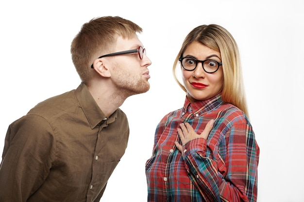 Шокированная девушка в стильной клетчатой рубашке и овальных очках, высовывая глаза, держа руку на груди, чувствуя ужас, пока какой-то ботаник собирается ее поцеловать, надувая губы и закрывая глаза
