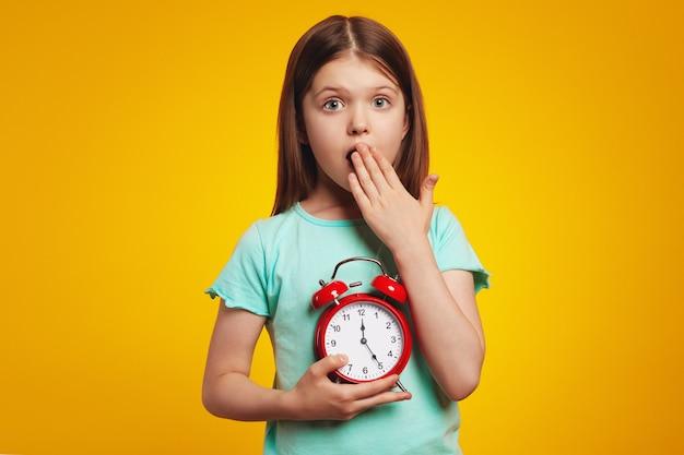 Шокированный ребенок девочка держит будильник на изолированном желтом фоне