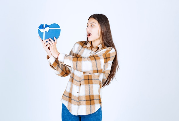 Shocked girl looking at surprise gift on white wall.
