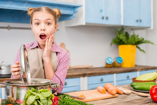 Shocked girl opening the lid of cooking pot in the kitchen looking at camera
