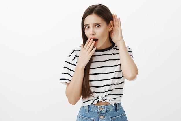 Потрясенная девушка разговаривает над головой, взволнованная женщина подслушивает или сплетничает