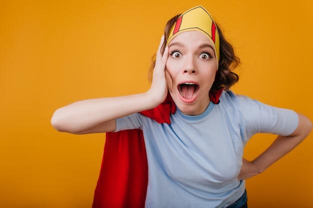 Ragazza scioccata con corona di carta che scherza durante il servizio fotografico in interni
