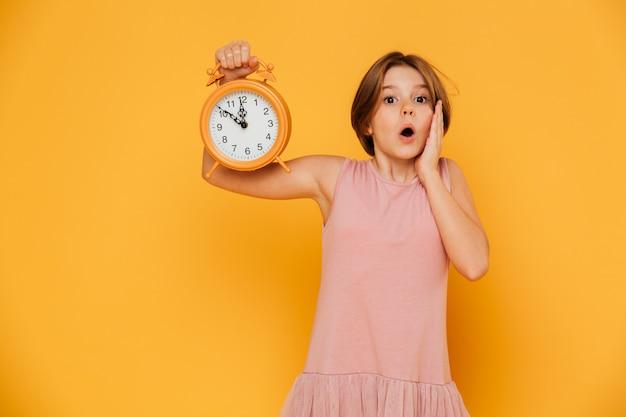 Сотрясенная девушка показывая будильник и смотря камеру при раскрытый изолированный рот