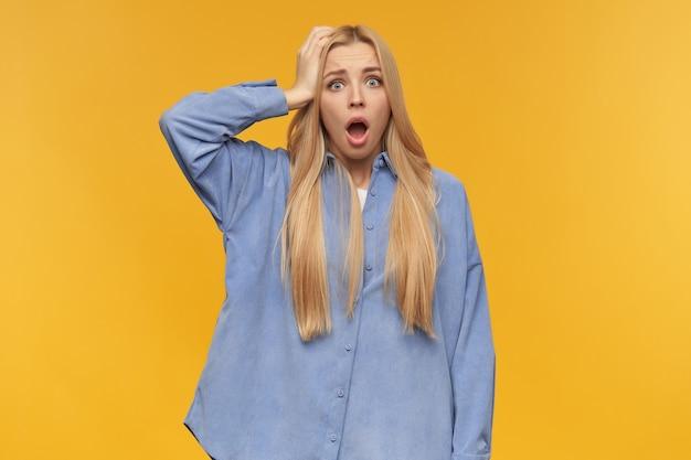 ショックを受けた女の子、金髪の長い髪の女性を強調しました。青いシャツを着ています。人と感情の概念。彼女の頭に触れて、何かを忘れました。オレンジ色の背景の上に分離されたカメラで見て