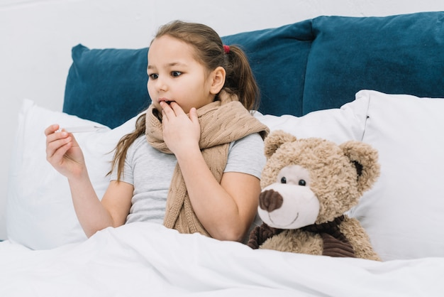 Shocked girl suffering from the cold and fever looking at thermometer
