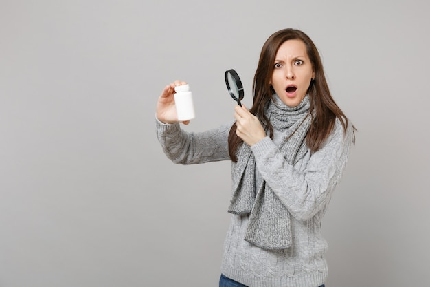 Shocked girl in sweater scarf looking on medication tablets aspirin pills in bottle with magnifying glass isolated on grey background. healthy lifestyle ill sick disease treatment cold season concept.