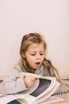 Shocked girl turning pages of book