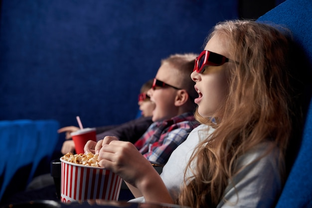 Shocked girl with friends watching film in movie house