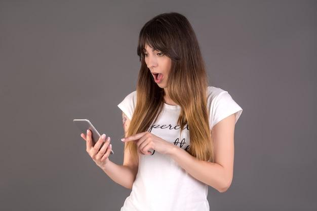 Шокированная девушка с мобильным телефоном