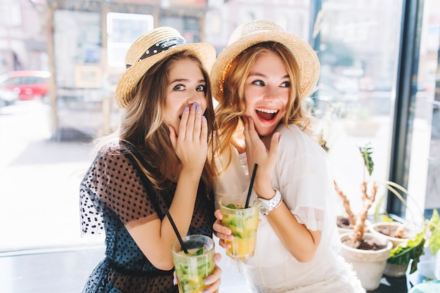 Shocked girls in hats holding glasses of cocktail looking away and emotionally covers faces