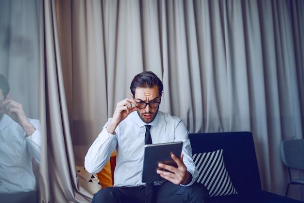 スーツとネクタイのオフィスでソファに座って、仕事でタブレットを使用してショックを受けた見栄えの良い白人のひげを生やした実業家。
