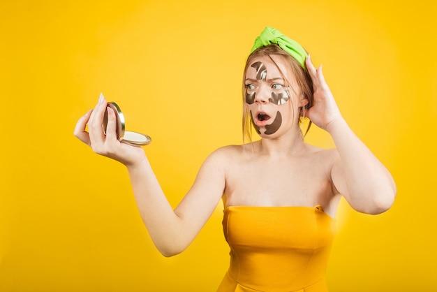 黄色の壁の分離面にパッチが付いたショックを受けたグリル。肌の悪いルーチンのストレスのある女性