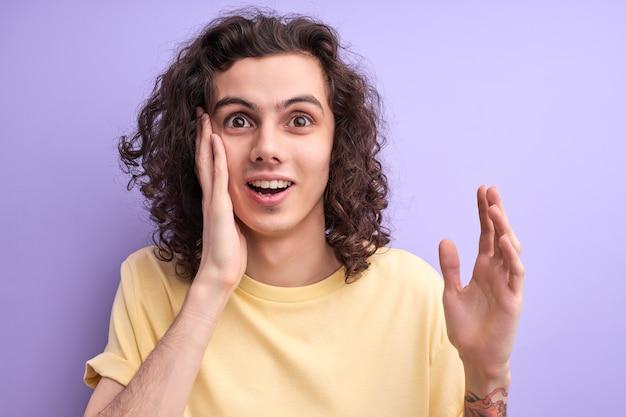 紫色の背景のスタジオの肖像画に分離されたカジュアルな黄色のtシャツでショックを受けた男。人々のライフスタイルの概念。コピースペースをモックアップします。口を開いたまま手を広げ、頬に触れる