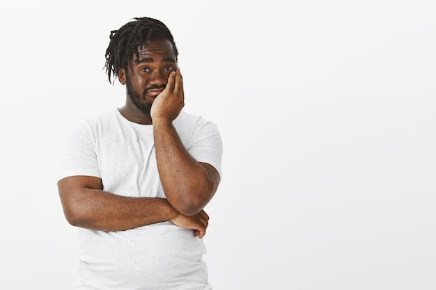 Shocked guy with braids posing against the white wall