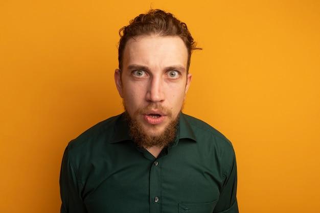 ショックを受けたハンサムなブロンドの男は、オレンジ色の壁に隔離された正面を見て