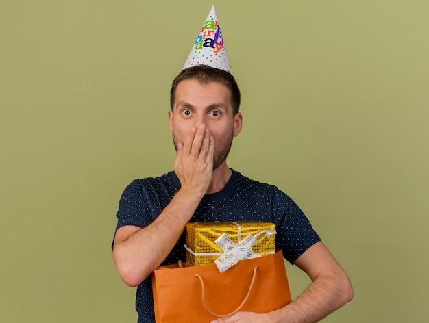 Berretto da portare di compleanno dell'uomo caucasico bello scioccato tiene il contenitore di regalo nel sacchetto della spesa di carta isolato su fondo verde oliva con lo spazio della copia