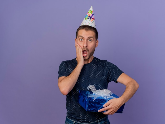 Shocked handsome caucasian man wearing birthday cap puts hand on face and holds gift box isolated on purple background with copy space