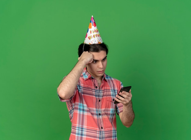생일 모자를 쓰고 충격을받은 잘 생긴 백인 남자가 이마를 잡고 전화를보고 손을 넣습니다.