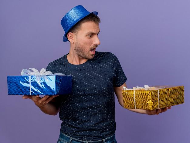 L'uomo caucasico bello scioccato che porta il cappello blu tiene e guarda i contenitori di regalo isolati su fondo viola con lo spazio della copia