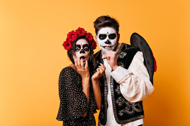 Shocked handsome guy with sombrero posing on yellow wall. emotional tanned girl in zombie attire fooling around in day of the dead.