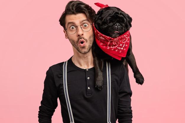 Scioccato bel proprietario maschio di cane, guarda con espressione terribile, scopre cattive notizie, essendo in compagnia di animali domestici, vestito elegantemente, posano insieme contro il muro rosa. emozioni, stile di vita