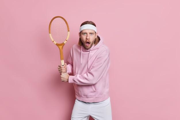 충격을받은 잘 생긴 남자 테니스 선수가 라켓과 함께 준비 위치에서 포즈를 취합니다.