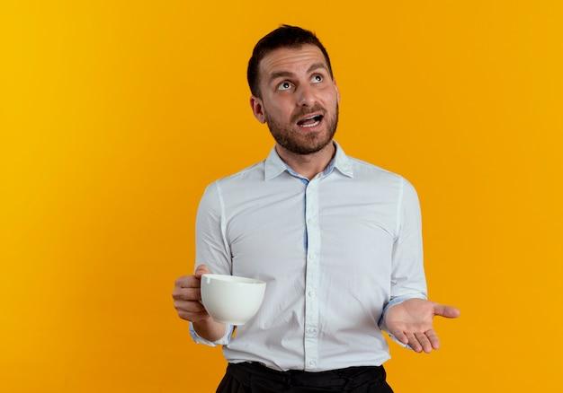 Uomo bello scioccato che tiene tazza che osserva in su isolato sulla parete arancione