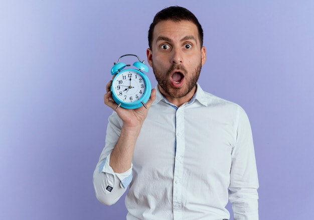 ショックを受けたハンサムな男は紫色の壁に分離された目覚まし時計を保持