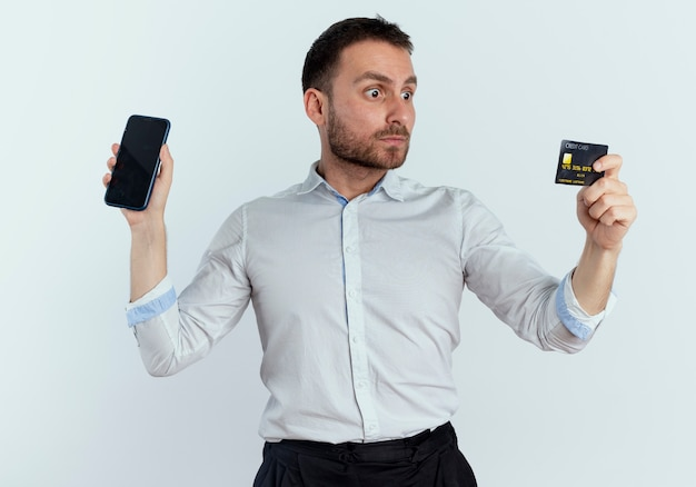 Shocked handsome man holds phone and looks at credit card isolated on white wall