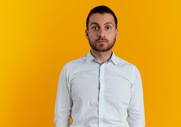 Uomo bello scioccato che sembra isolato sulla parete arancione