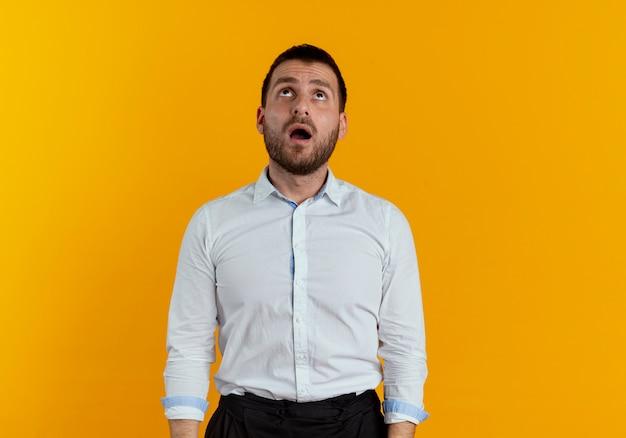 L'uomo bello scioccato osserva in su isolato sulla parete arancione