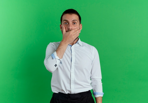 Shocked handsome man puts hand on mouth isolated on green wall