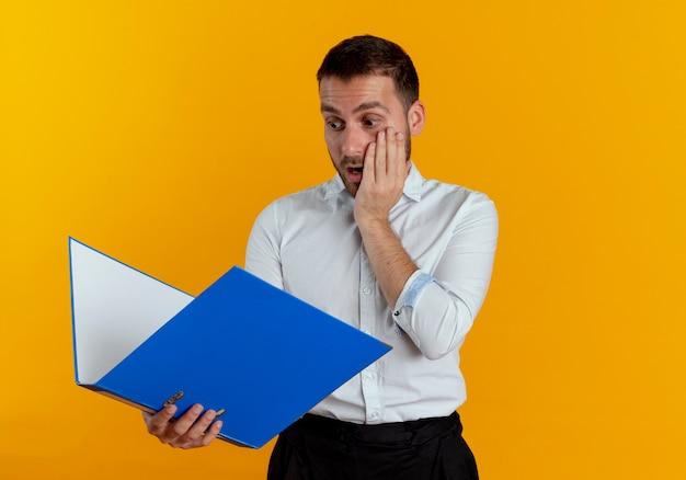 Шокированный красавец кладет руку на лицо, держа и глядя на папку с файлами, изолированную на оранжевой стене