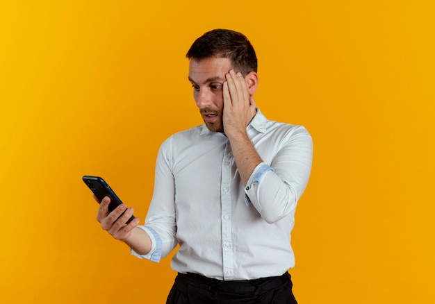 Шокированный красавец кладет руку на лицо, держа и глядя на телефон, изолированный на оранжевой стене